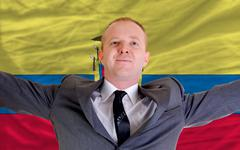 happy businessman because of profitable investment in ecuador standing near f - stock photo