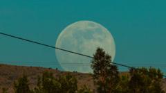 Stock Video Footage of HD 30p  tight track Supermoon 2013 rising over ridge near Tucson AZ Time Lapse