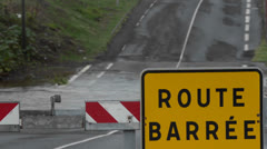 A road sign in French indicates that the road is closed during a big storm. - stock footage