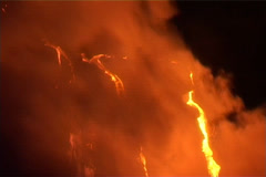 Rivers of lava flow down a volcanic slope while smoke rises. Stock Footage