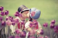 Two kissing vintage dolls in tulip garden. Stock Photos
