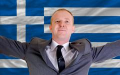 Stock Photo of happy businessman because of profitable investment in greece standing near fl