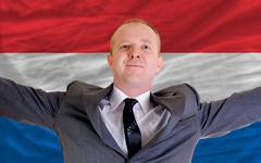 Stock Photo of happy businessman because of profitable investment in holland standing near f