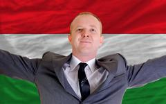 Stock Photo of happy businessman because of profitable investment in hungary standing near f