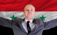 Stock Photo of happy businessman because of profitable investment in iraq standing near flag