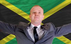 Happy businessman because of profitable investment in jamaica standing near f Stock Photos