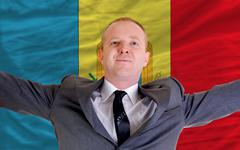 Stock Photo of happy businessman because of profitable investment in moldova standing near f