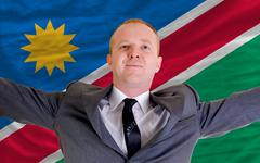 Stock Photo of happy businessman because of profitable investment in namibia standing near f