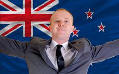 Stock Photo of happy businessman because of profitable investment in new zealand standing ne