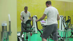Young man at the gym exercising on the xtrainer machines Stock Footage