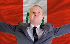 happy businessman because of profitable investment in peru standing near flag - stock photo