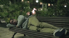Young man sleeping on bench in tourist resort at night Stock Footage