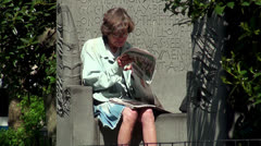 Grandma reads the newspapers in Madison Square Park. Stock Footage