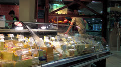 Shoppers in a grocery supermarket. Department of cheeses. Stock Footage