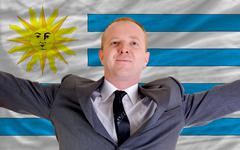 Stock Photo of happy businessman because of profitable investment in uruguay standing near f