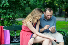Young happy couple with smartphone sitting in the park NTSC Stock Footage