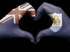 Stock Photo of heart and love gesture by hands colored in anguilla flag for tourism