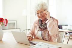 Mature woman at home using laptop Stock Photos