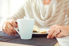 Wrinkled hands with a cup of coffee Stock Photos