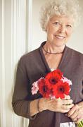 Senior woman holding a bouquet of fresh flowers Stock Photos