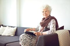 grandmother at home sitting on the couch - stock photo