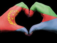 Stock Photo of heart and love gesture by hands colored in eritrea flag  for tourism