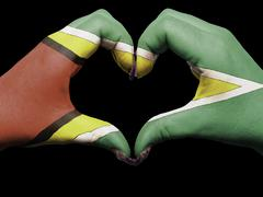 heart and love gesture by hands colored in guyana flag for tourism - stock photo