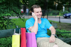 Man with shopping bags talking on cellphone in park NTSC Stock Footage