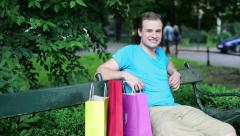 Happy man with shopping bags in the park HD Stock Footage
