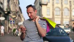 Man with smartphone and shopping bags in the city HD Stock Footage