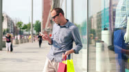 Stock Video Footage of Man with smartphone and shopping bags in the city HD
