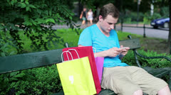Man with smartphone and shopping bags in the park HD Stock Footage