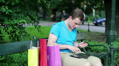 Man doing online shopping on tablet in the park HD Stock Footage