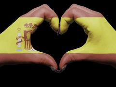 heart and love gesture by hands colored in spain flag for tourism - stock photo