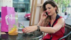 Beautiful woman talkin on cellphone in cafe HD Stock Footage