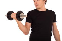 Man doing exercise with a steel dumbbell Stock Photos
