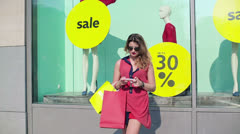Glamour woman using smartphone by shop window HD - stock footage