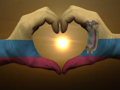 Heart and love gesture by hands colored in ecuador flag during beautiful sunr Stock Photos
