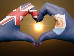 Stock Photo of heart and love gesture by hands colored in anguilla flag during beautiful sun