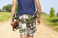 Stock Photo of Boy with skateboard and slingshot in pocket on rural road in summer