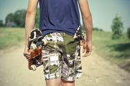 Stock Photo of Boy with skateboard and slingshot in pocket on rural road