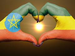 Heart and love gesture by hands colored in ethiopia flag during beautiful sun Stock Photos