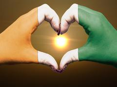 Heart and love gesture by hands colored in ivory coast flag during beautiful  Stock Photos