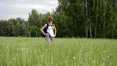 Stock Video Footage of Young woman walking in a field with a backpack