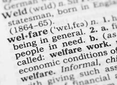 macro image of dictionary definition of welfare - stock photo