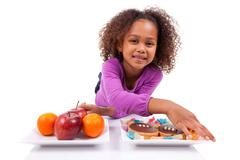 Little african asian girl hesitating between fruits or  candy Stock Photos