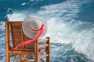Stock Photo of hat hanging on a chair against the sea waves