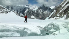 Climber crosses large crevasse above camp one - stock footage