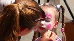Artist paints on face of little girl Stock Footage