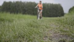 Woman in orange t-shirt with bicycle in summer field Stock Footage